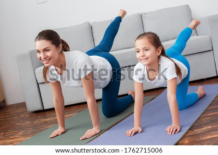 Sporty Concept! Beauty active young woman with daugther do balance exercise bird dog. Workout wearing blue sportswear, studio home room background. Practicing yoga on mat. Asana sunbird chakravakasana
