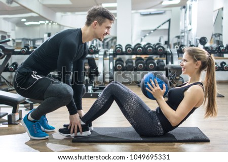Sporty couple exercising together in gym. Handsome man assisting beautiful girl while doing sits ups with medicine ball in fitness centre. #1049695331