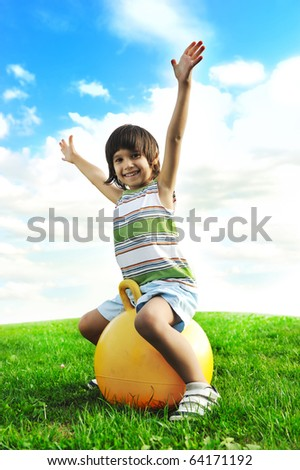 Sporty cute positive kid, playing happily with big ball on green meadow - stock photo