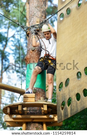sporty, cute, young boy in white t shirt in the adventure rope activity park with helmet and safety equipment. Boy plays and has fun doing activities outdoors. Hobby, active lifestyle concept #1154259814