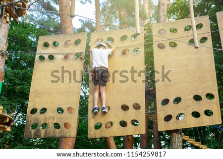 sporty, cute, young boy in white t shirt in the adventure rope activity park with helmet and safety equipment. Boy plays and has fun doing activities outdoors. Hobby, active lifestyle concept #1154259817