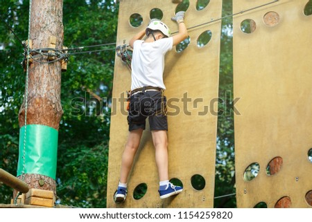 sporty, cute, young boy in white t shirt in the adventure rope activity park with helmet and safety equipment. Boy plays and has fun doing activities outdoors. Hobby, active lifestyle concept #1154259820