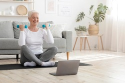 Sporty elderly lady training at home with dumbbells, watching online tutorials on laptop, copy space