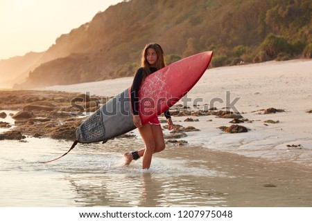 Sporty European woman in wetsuit, carries big surfboard, being fastened with leash to feel safe, looks thoughtfully aside, returns home after active day and hiting waves, cliff in background #1207975048