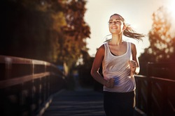 Sporty female jogger running and training outside in nature