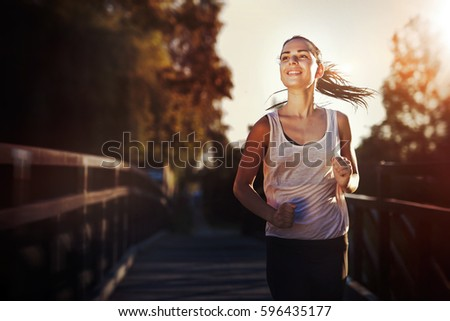 Sporty female jogger running and training outside in nature #596435177