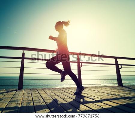 sporty female runner running on seaside boardwalk during sunrise