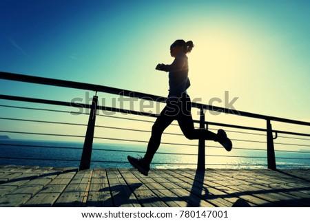 sporty female runner running on seaside boardwalk during sunrise #780147001