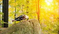 Sporty fit woman is practicing yoga and doing asana Vakrasana in autumn park on the big boulder