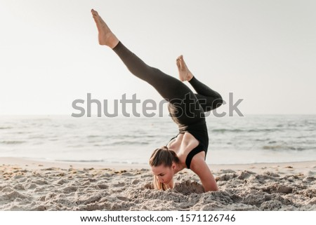 sporty fit yogi woman practice handstand in beautiful asana in the sand near ocean