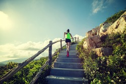 sporty fitness woman runner running upstairs on mountain top