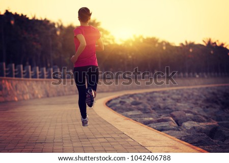 Sporty fitness woman running on sunrise seaside trail  #1042406788