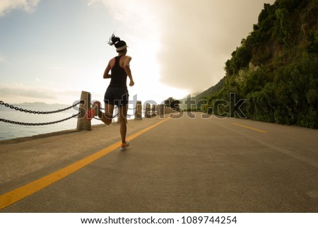 Sporty fitness woman running on sunrise seaside trail #1089744254