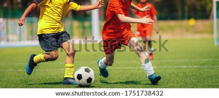 Photo of  Sporty Football Boys Running After Ball in Duel. School Soccer Competition Between Two Junior Level Players. Multi-ethnic Kids Play Sports