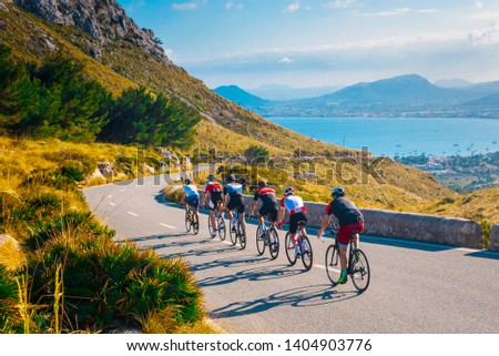 Sporty friends on bicycle on sunset light in beautiful nature by the sea. Road cycling on the coast. Sport in Nature background. Teamwork concept photo