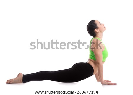 Sporty girl doing exercises for flexible spine on white background, yoga asana from Surya Namaskar sequence, Sun Salutation complex, urdhva mukha shvanasana (upward facing dog pose)