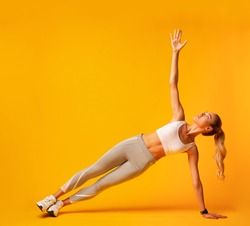 Sporty Girl Doing Side Plank Exercise During Workout Over Yellow Background. Studio Shot