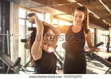 Photo of  Sporty girl doing weight exercises with assistance of her personal trainer at gym.