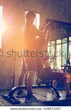 Sporty girl doing weight exercises with assistance of her personal trainer at public gym.