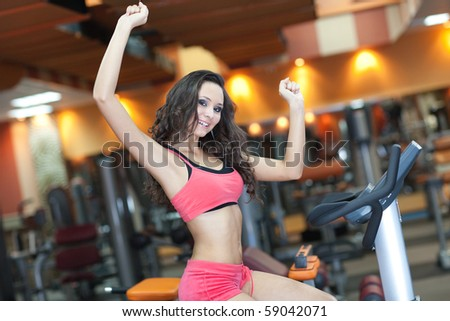 Sporty Girl in fitness hall is cycling, healthy concept - stock photo