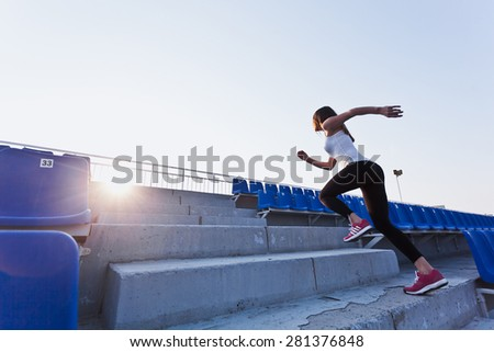 Sporty girl in white shirt running fast to a sunset on a stadium. Side view. Dynamic photo. Young woman in sportswear training on a stadium. Copy space. Sport lifestyle concept Stock photo ©