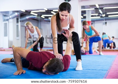 sporty girl is doing self-defence moves with coach in sporty gym. Stock photo ©