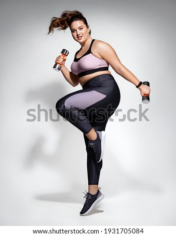 Sporty girl jumping with dumbbells. Photo of model with curvy figure in fashionable sportswear on grey background. Dynamic movement. Side view. Sports motivation and healthy lifestyle Photo stock ©