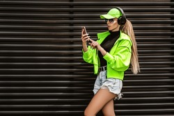 Sporty girl shooting selfie. Beautiful woman in trendy sportswear and earphones.  Attractive woman doing selfie shot on mobile phone.