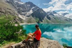 Sporty Girl sitting enjoying beautiful view of mountain lake near Kaprun,Austria.Quiet relaxation outdoors.Wonderful nature landscape,turquoise water,holiday travel scene.Wanderlust happy woman