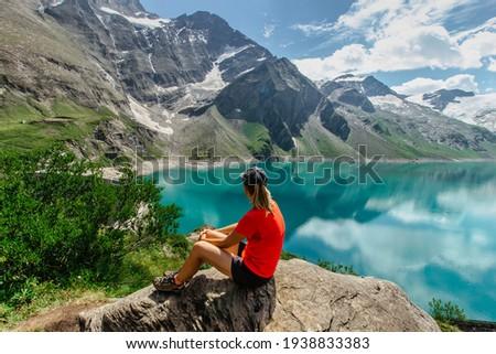 Sporty Girl sitting enjoying beautiful view of mountain lake near Kaprun,Austria.Quiet relaxation outdoors.Wonderful nature landscape,turquoise water,holiday travel scene.Wanderlust happy woman ストックフォト ©