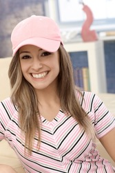 Sporty girl smiling in pink baseball cap at home.