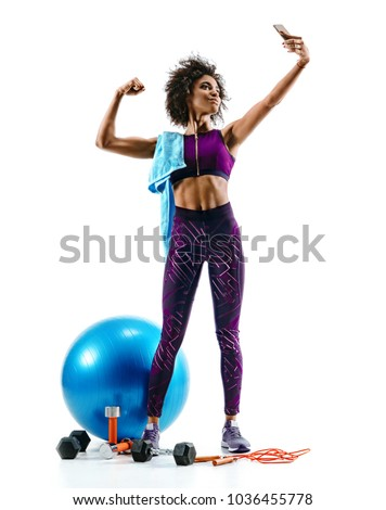 Sporty girl taking selfie pictures on smartphone with sports accesories on white background. Strength and motivation. Full length