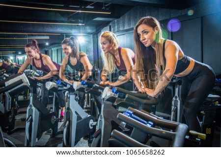 Sporty girls riding exercise bikes in gym #1065658262