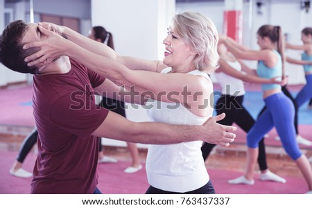 Sporty glad cheerful positive mature woman with her instructor are training self-defence moves in gym. Stock photo ©