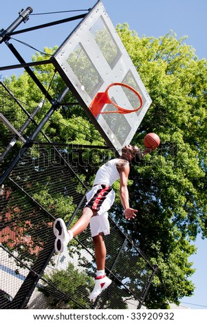 Sporty handsome African-American man dressed in white jumping in the air reaching for the basket while playing basketball in an outdoor court on a summer day trying to dunk the ball
