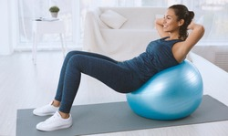 Sporty Hispanic woman doing abs exercises on fitness ball at home