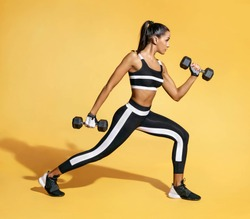Sporty latin woman in black sportswear holding dumbbells. Photo of muscular woman in training pumping up muscles of hands and legs on yellow background. Strength and motivation. Side view
