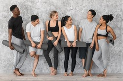 Sporty Lifestyle Concept. Group of athletic multiracial barefoot people resting with yoga mats before training in studio, standing near grey wall, wearing comfortable sportswear, smiling to each other