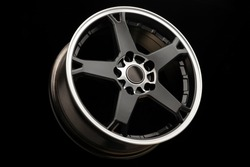 sporty light black alloy wheel with a white matte rim, close-up.