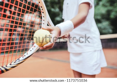 Sporty little girl preparing to serve tennis ball. Close up view of beautiful yong girl holding tennis ball and racket. Child tennis player preparing to serve.