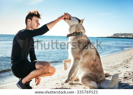 sporty male playing with two husky dogs on beach