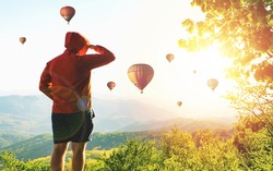 Sporty man and a lot of hot air balloons. The feeling of complete freedom, achievement, achievement, happiness. Enjoy moment of people hiking standing on mountain. Balloons flying over mountain