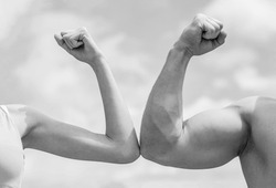 Sporty man and woman. Muscular arm vs weak hand. Vs, fight hard. Competition, strength comparison. Rivalry concept. Hand, man arm fist Close-up. Black and white.