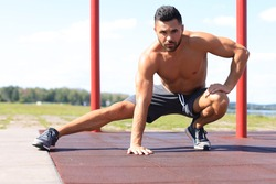 Sporty man doing workout stretching exercises for legs outdoors