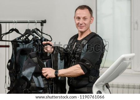 Sporty man hanging electro muscle stimulation vests on rack #1190761066