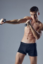 sporty man inflated torso dumbbells in hand workout