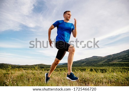 sporty man runner running on mountain plateau in summer