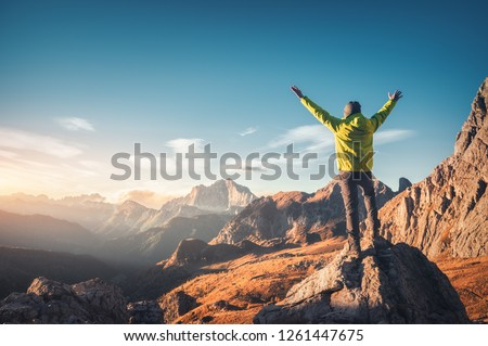 Sporty man standing on the stone with raised up arms against mountain valley at sunset. Happy young man, rocks, autumn forest and blue sky in Dolomites, Italy. Traveler hiking in alpine mountains #1261447675