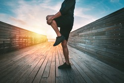 Sporty man warming up and stretching legs before workout outdoors at sunset or sunrise. Stretching gluteus maximus muscle. Athletic man doing fitness stretching exercises. Sport and healthy lifestyle