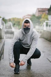 Sporty man wearing face mask for protection against coronavirus and pollution during winter running and outdoor fitness workout under the rain. Sportsman lacing sport shoes on urban stairs.